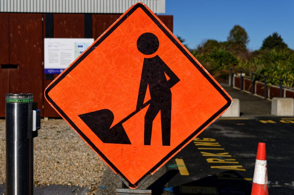 An orange diamond sign with a figure of a person at work warns of potential danger