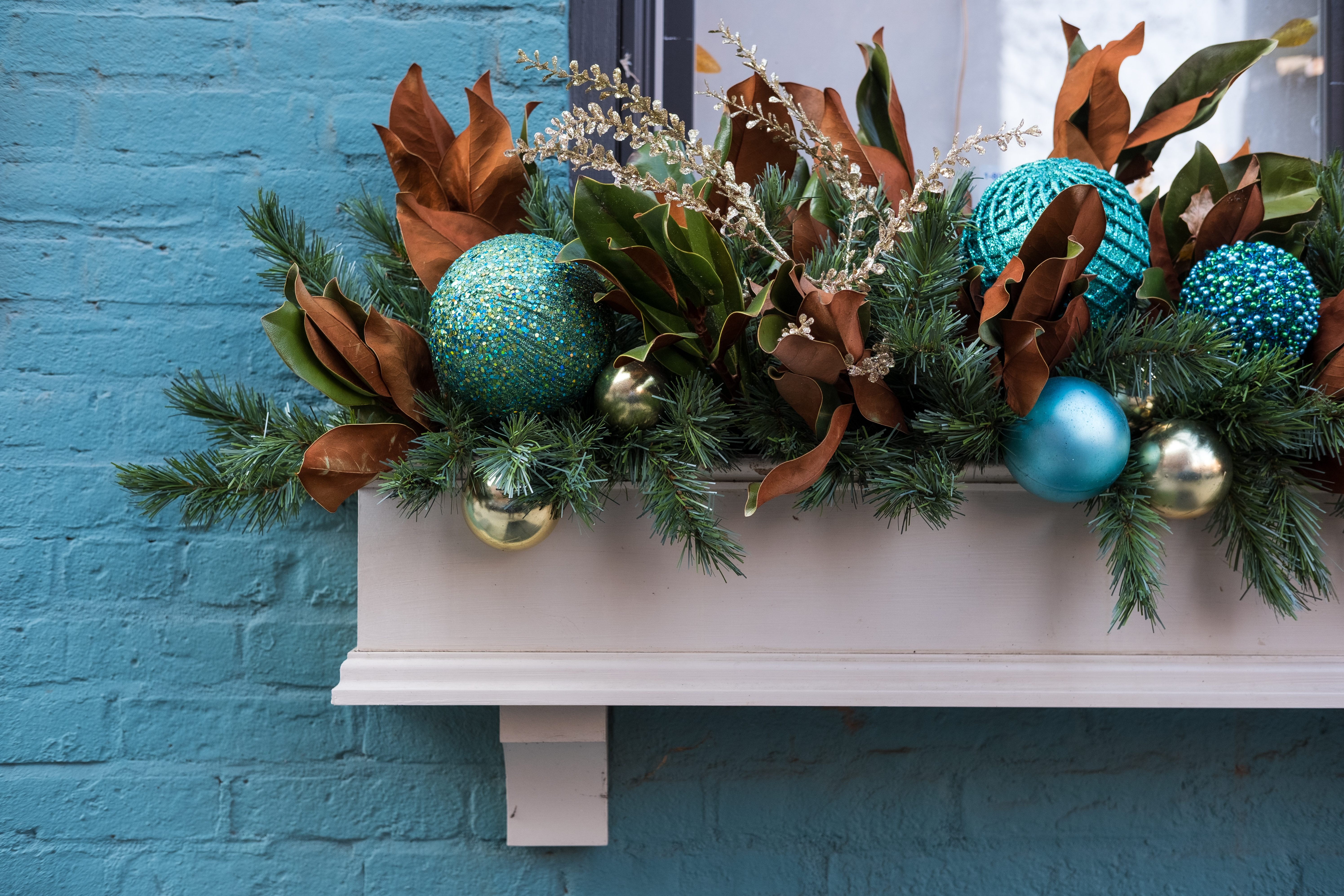 A close-up of the left side of a window planter box decorated for Christmas, set against a bright blue brick building.