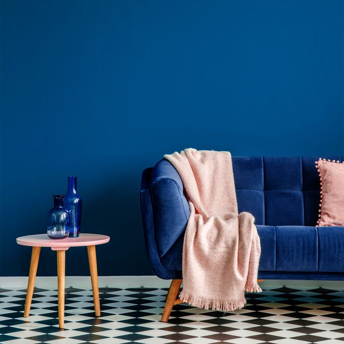 living room with blue wall and blue couch