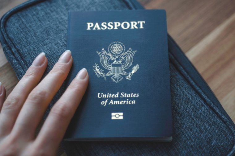 Woman's fingers holding Passport of USA (United States of America) on blue travel wallet and wooden background.