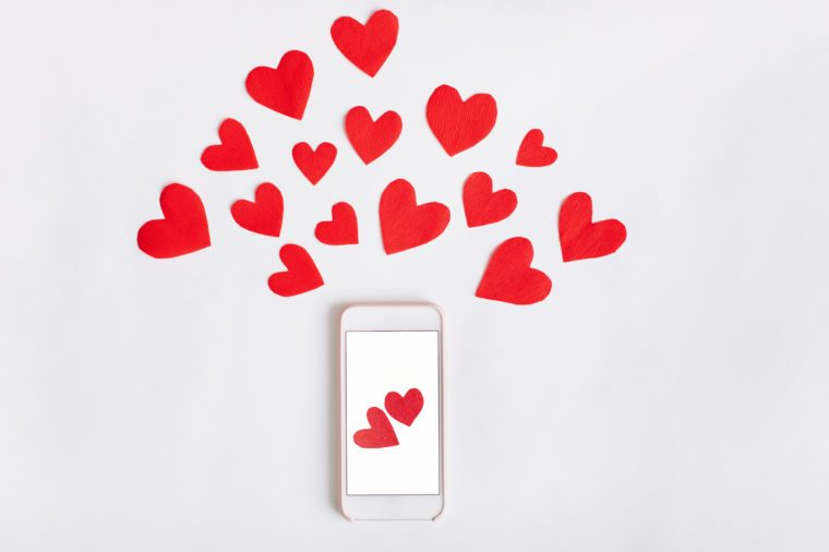 Top view of mobile phone with blank screen and red paper hearts on white background. Flat lay. Mockup template for Valentines Day.
