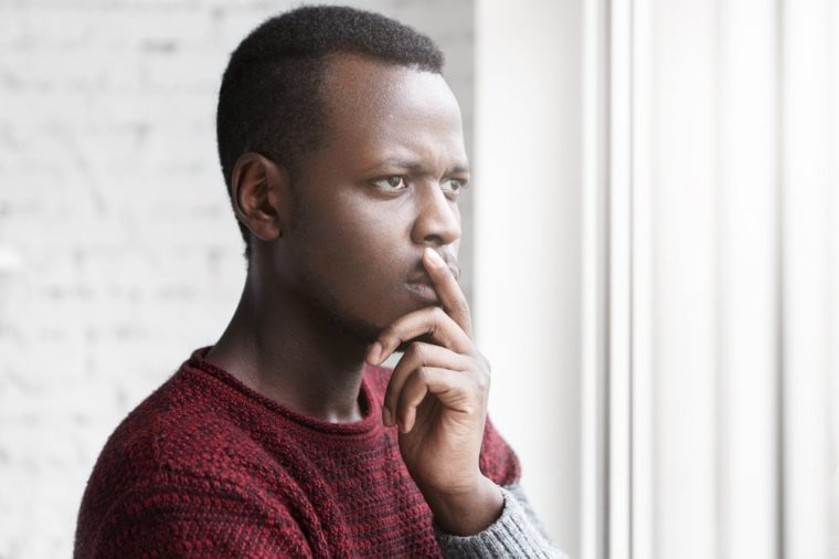 Half profile portrait of handsome young African American writer looking through window with pensive and doubtful facial expression, touching his chin while thinking over the end of his new book