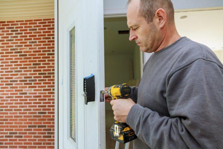 Installation locked interior door woodworker hands install lock Installation of the door lock.