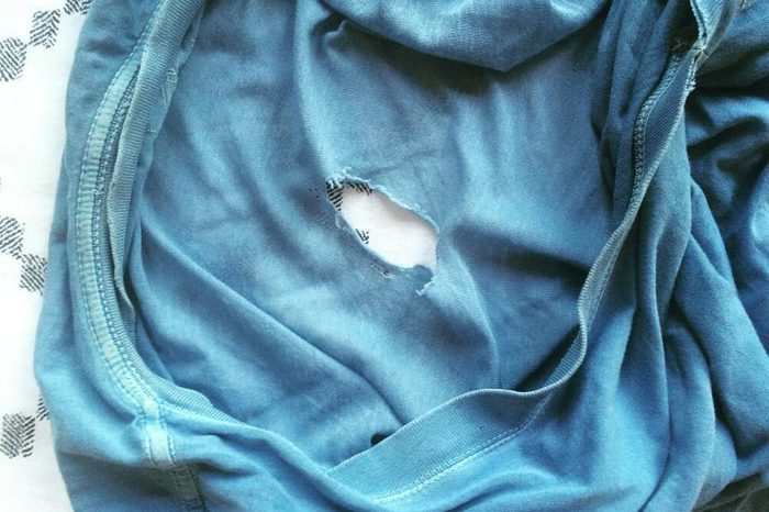 Old, worn blue t-shirt with hole