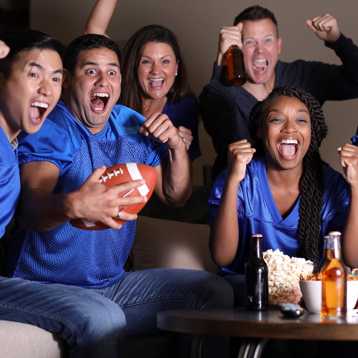 Football fans watching the game at home on television
