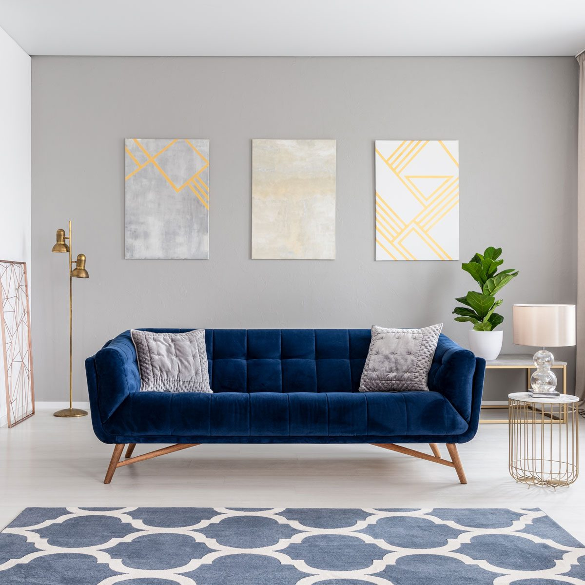 navy blue sofa in the middle of a bright living room interior with gold metal side tables and three paintings on a gray wall couch pillows