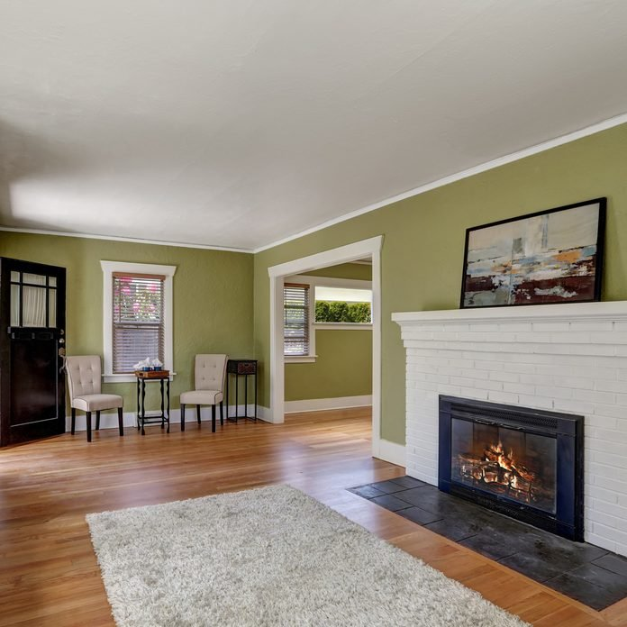 Living-room-interior-design-of-craftsman-home-with-white-brick-fireplace-built-in-shelves-window-seat-with-pillows-pale-green-walls-and-hardwood-floor