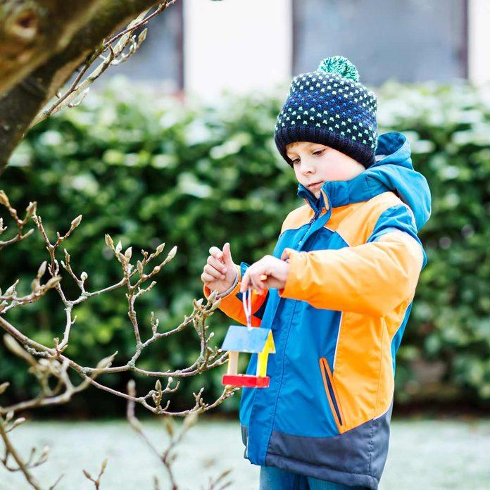 child and bird feeder
