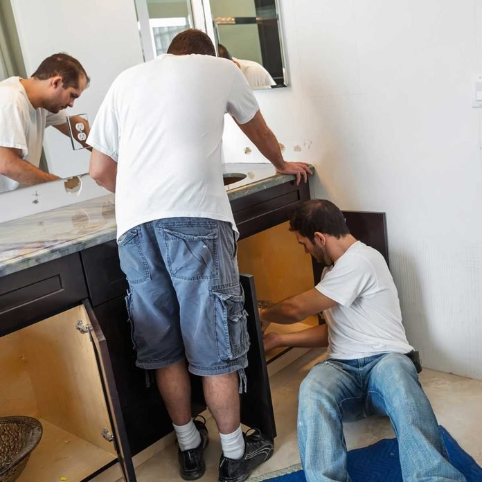 Two men installing a bathroom vanity