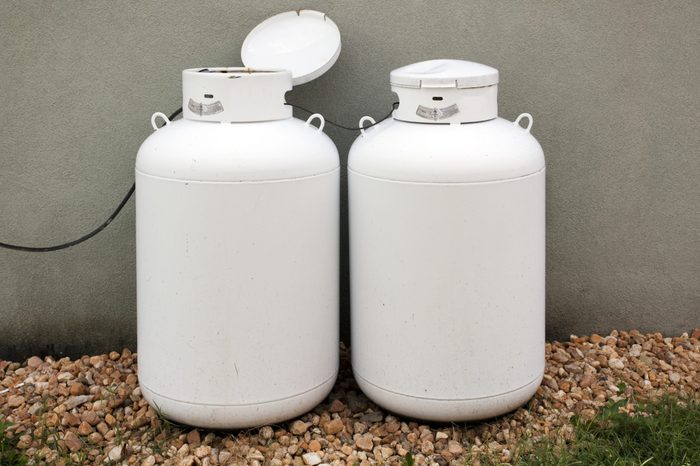 Two home use propane tanks stored outside against building wall with a gravel foreground. Horizontal.