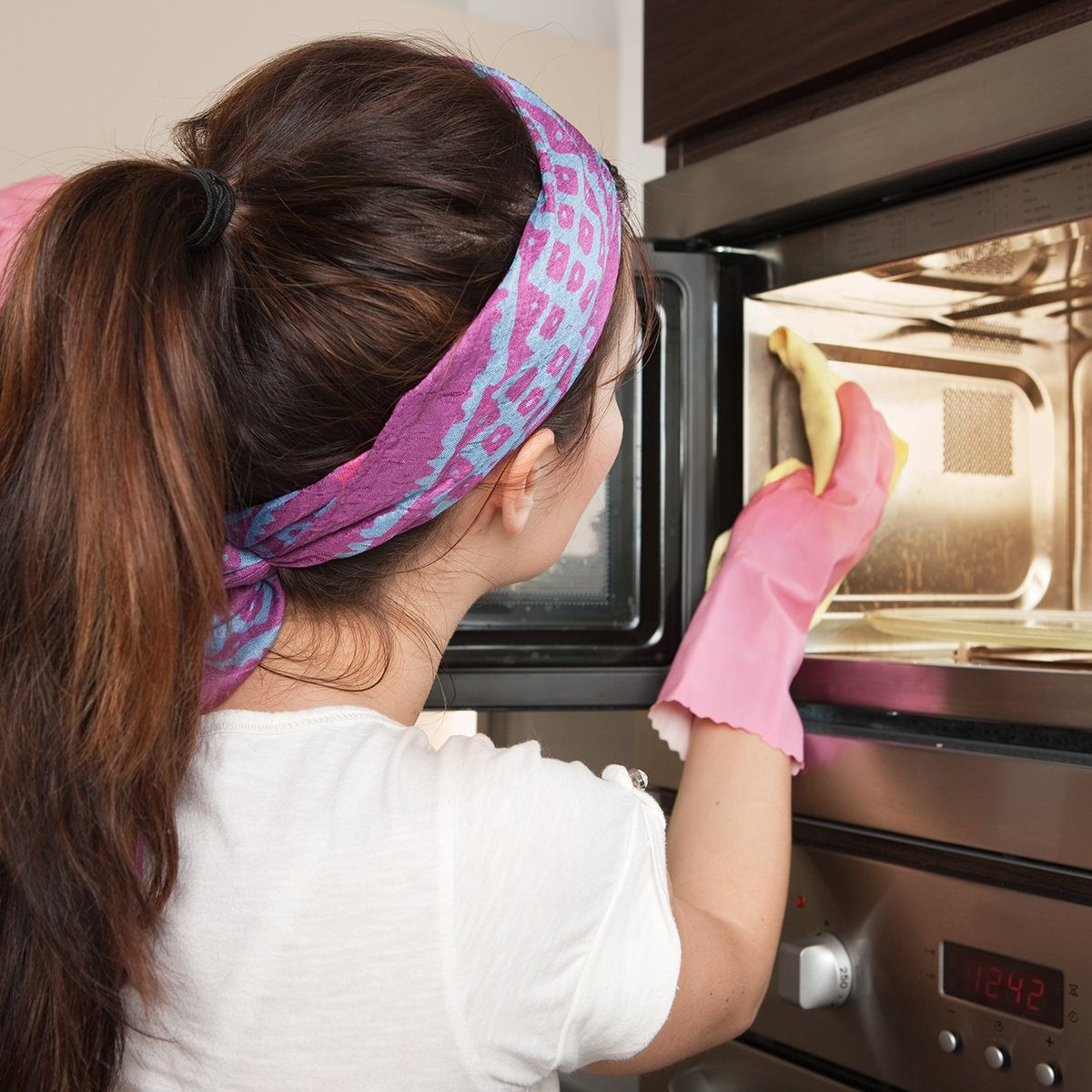 Girl cleaning oven in the kitchen