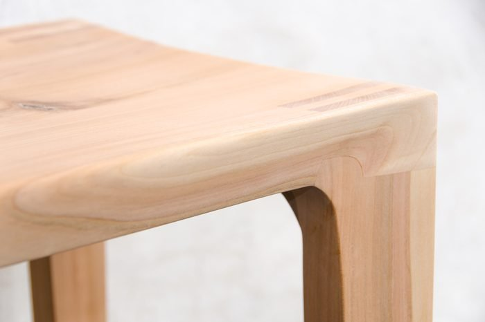 Detail of a wooden glued joint of a chairs leg. Material used for the stool is cherry wood untreated with a sanded finish