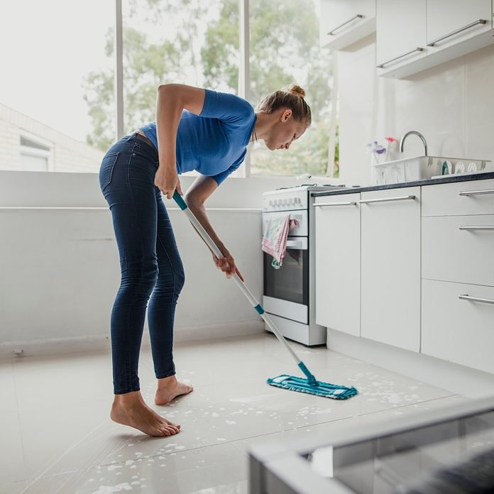 Young female cleaning the floor in the kitchen.