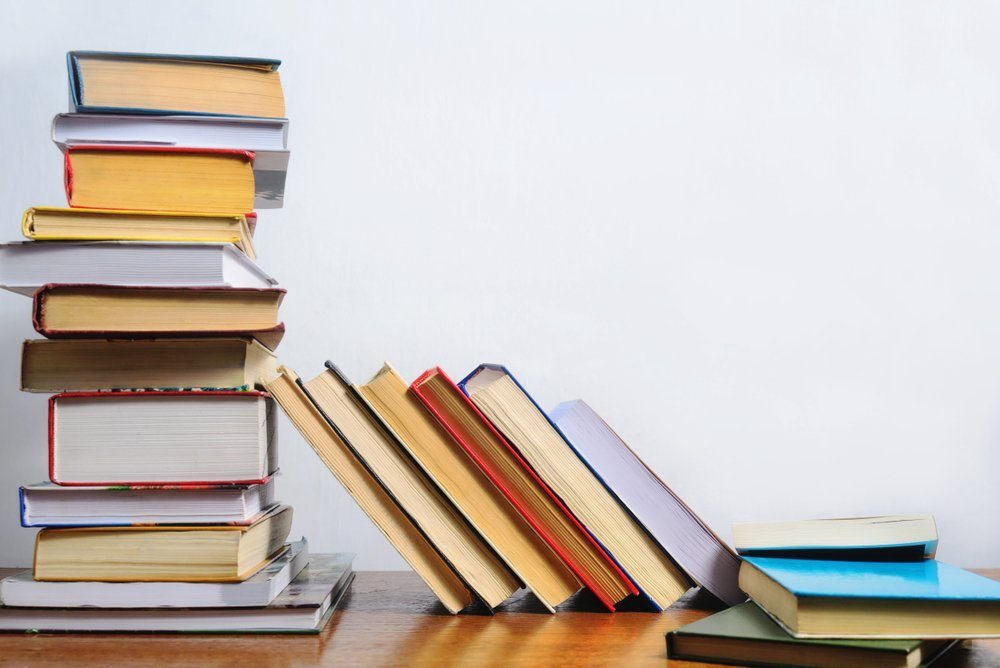 Stack of different books on a table against a white wall background