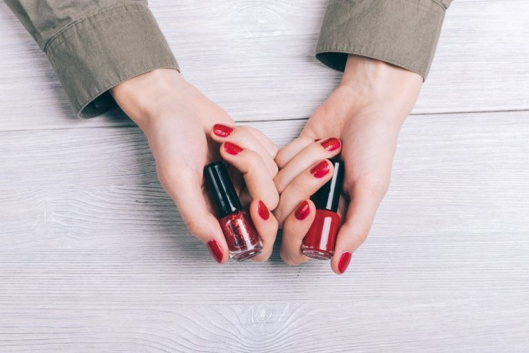 Bottles with red nail polish in female hands top view