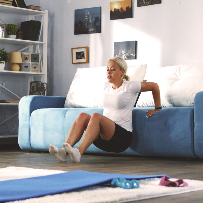 Woman perforing tricep dips on a couch