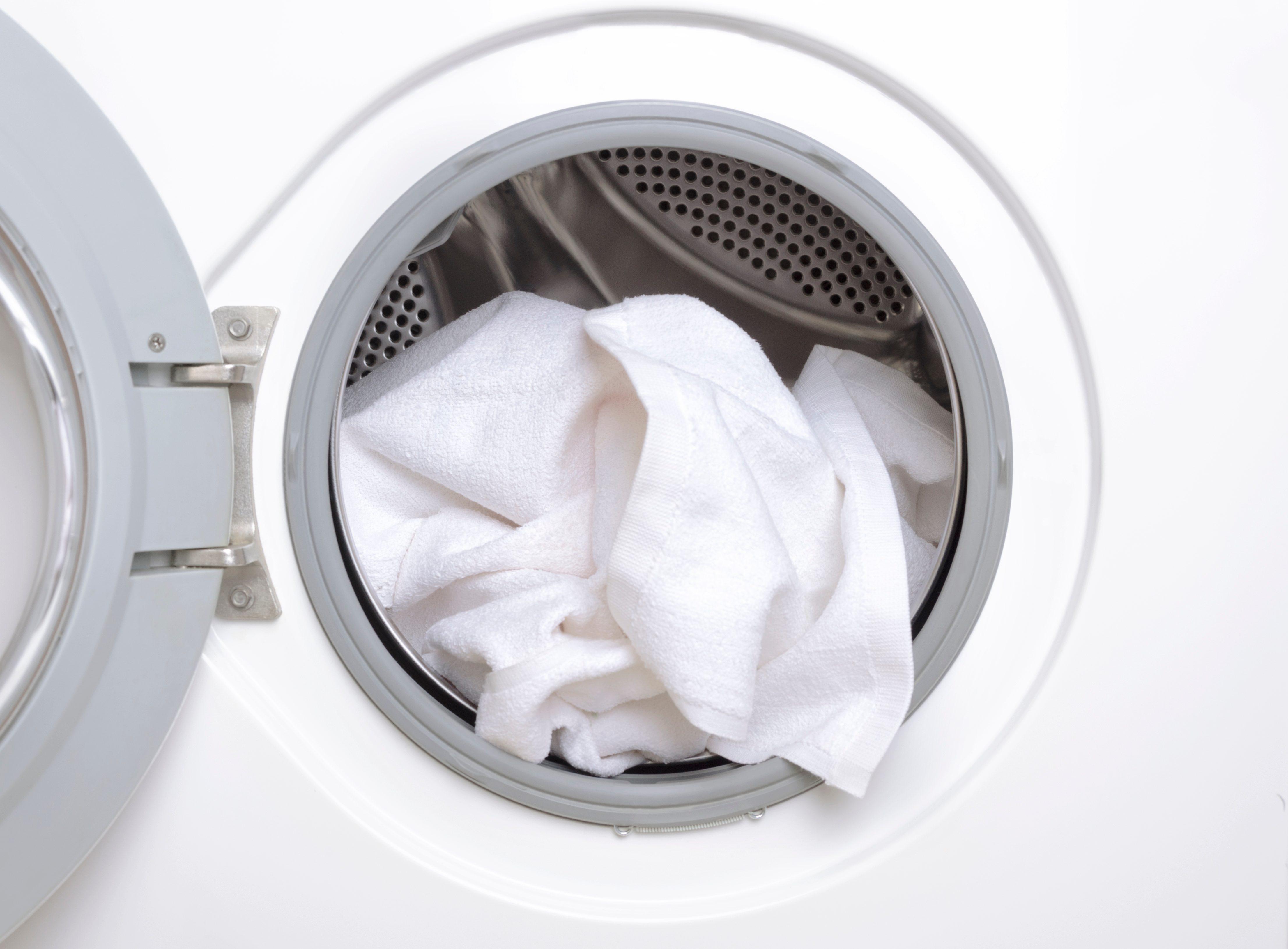 Finishing a part house, washing the white towels.Closeup of washing machine drum