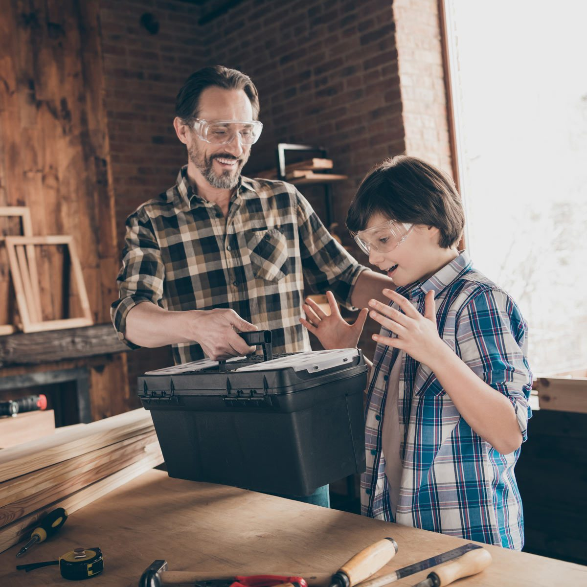 woodworkers master handyman dad giving new toolkit to son surprised