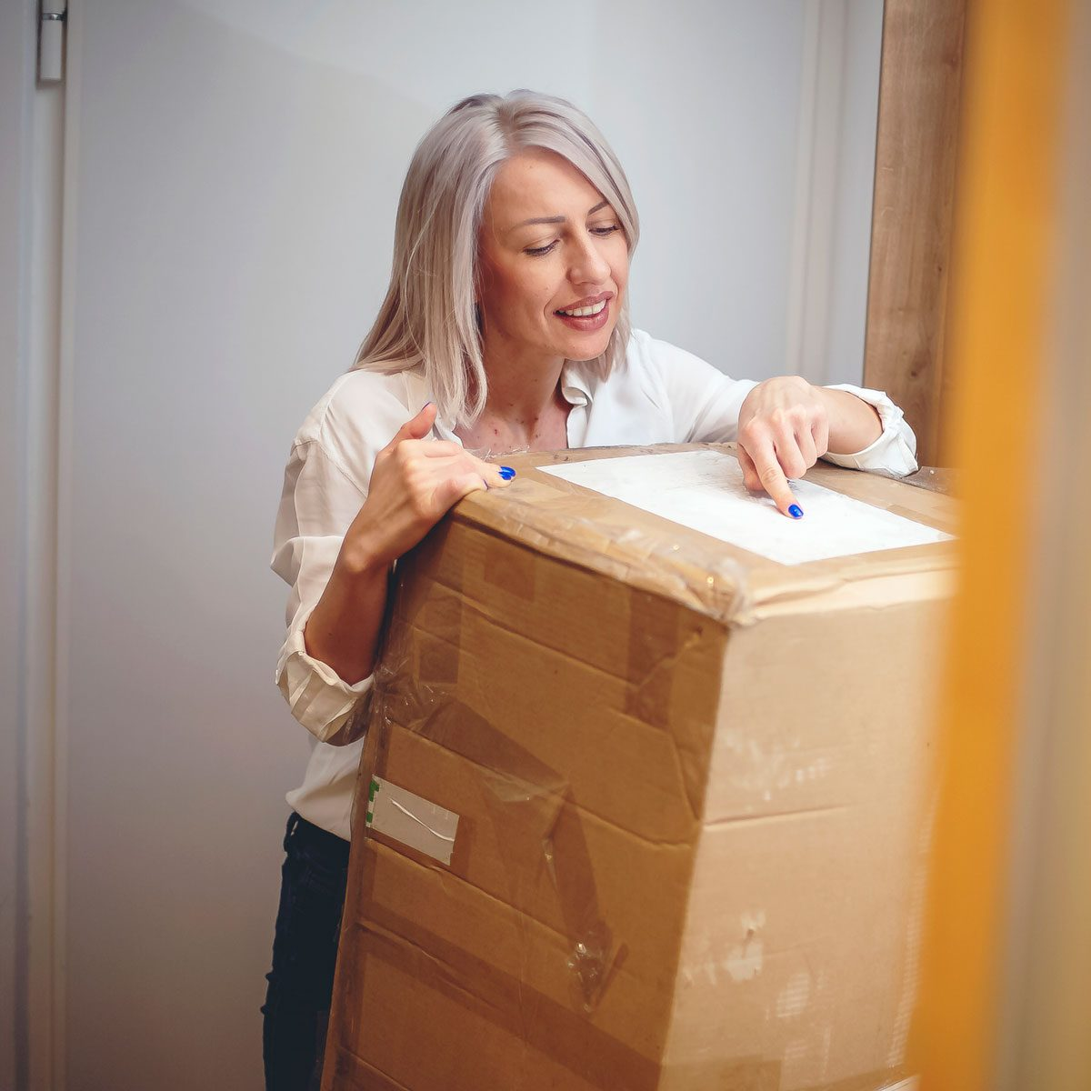 Woman receiving package from a building materials delivery service