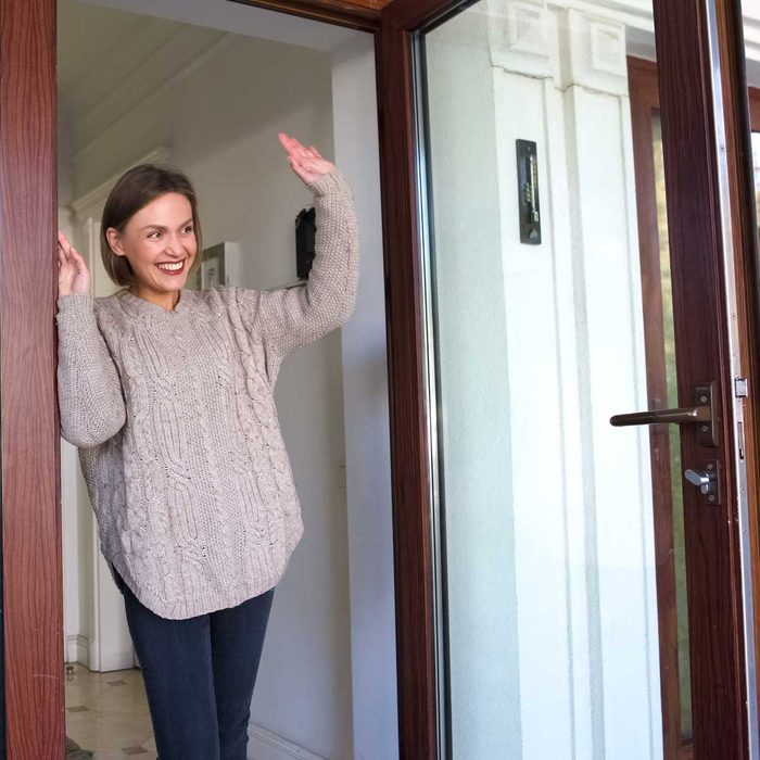 Woman waving in a doorway