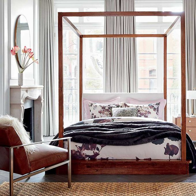 Bedroom with four poster bed and floral blanket.
