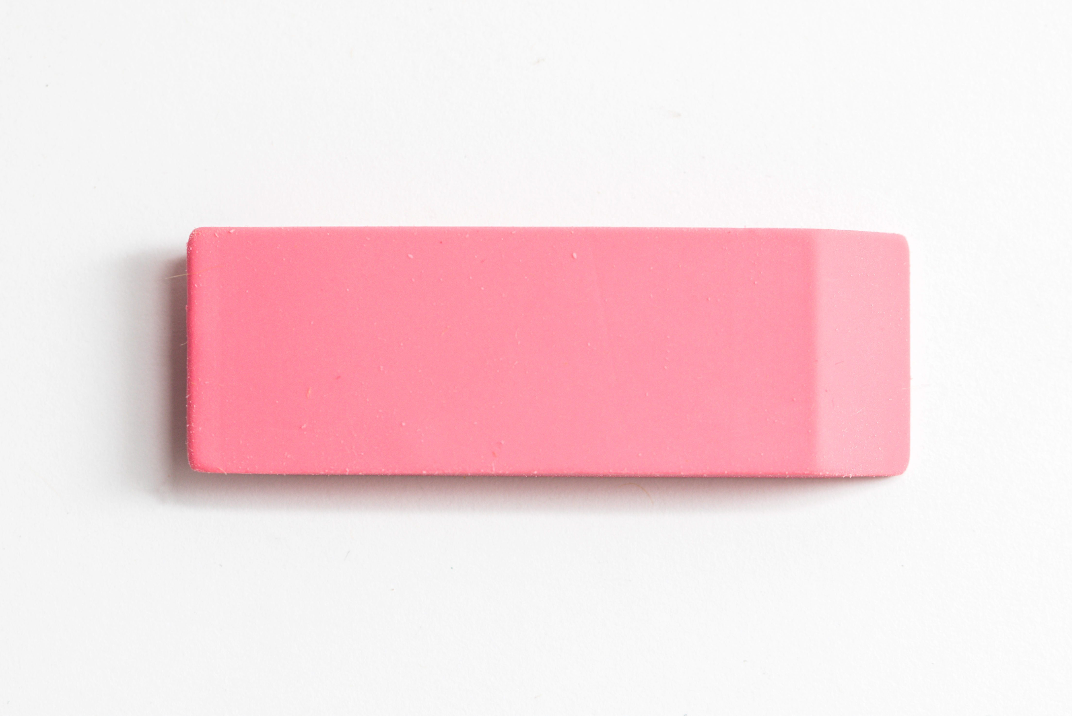 Pink eraser shot up close against a white background