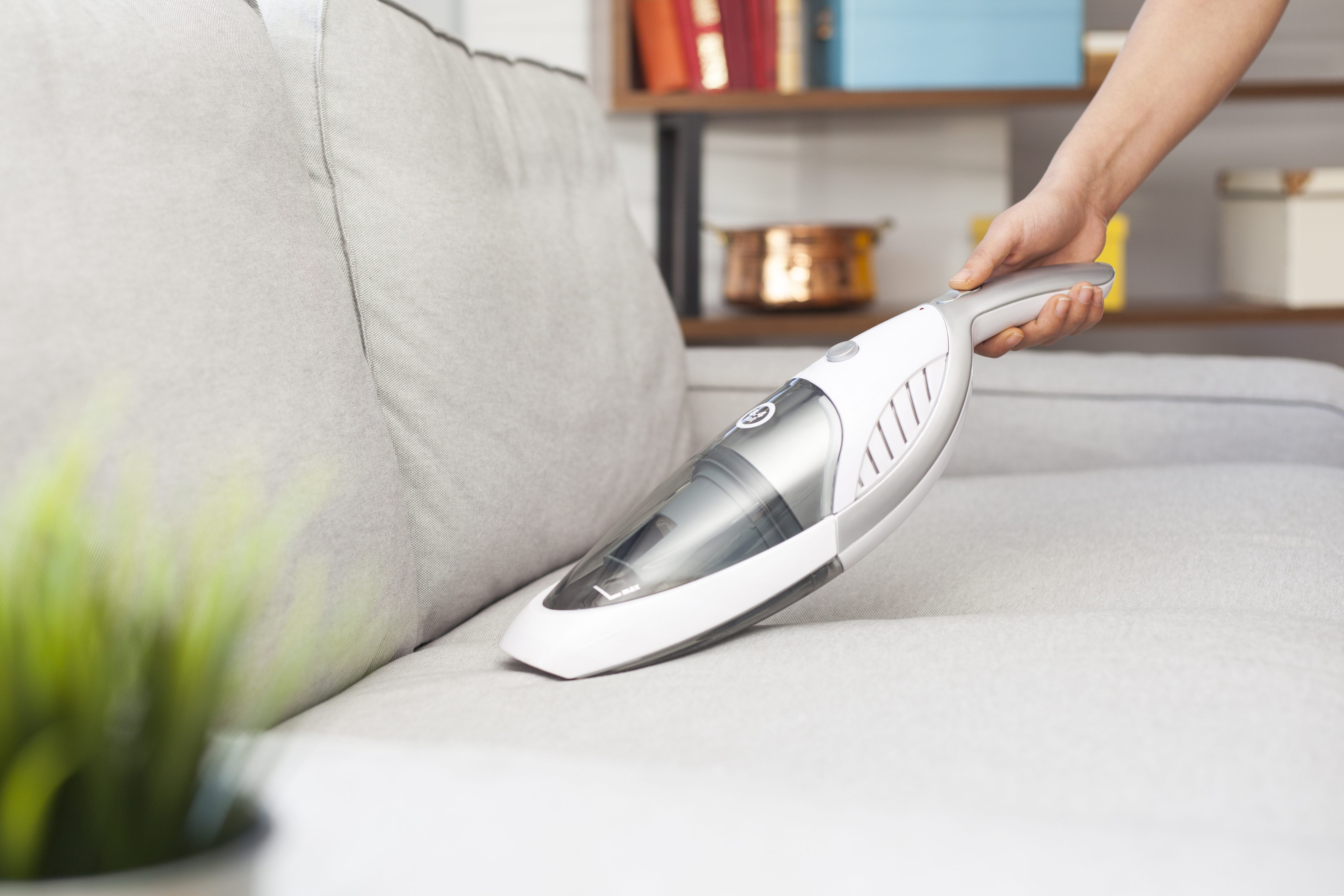 Woman with handheld vacuum cleaning on sofa; Shutterstock ID 511880752