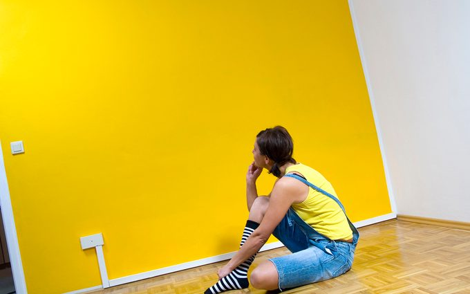 Woman sitting on floor, looking at yellow wall
