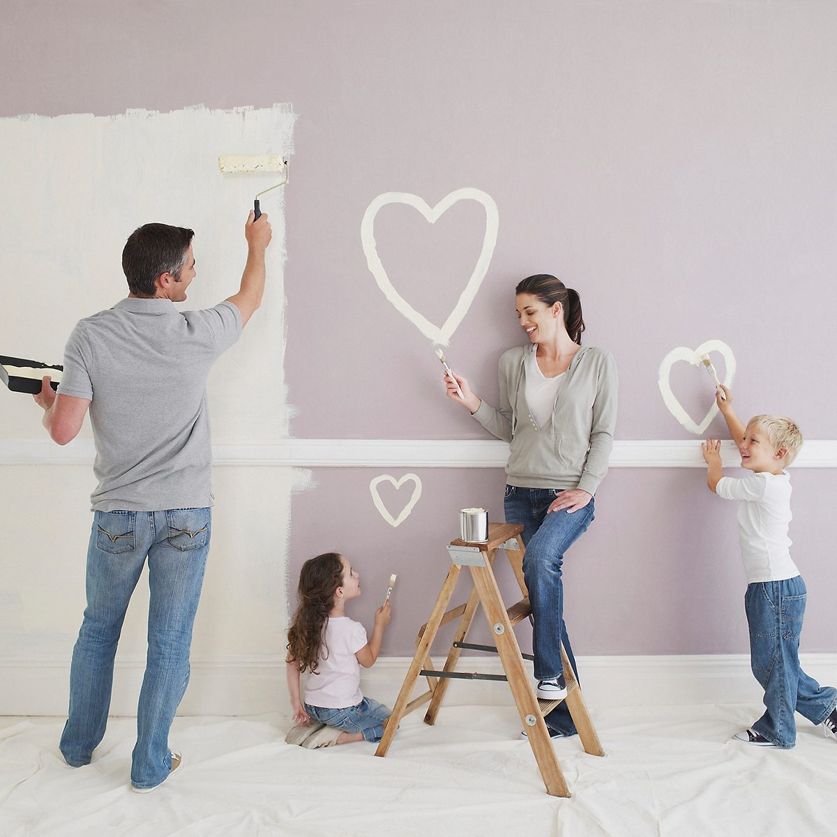 Man and woman with boy and girl painting hearts on wall