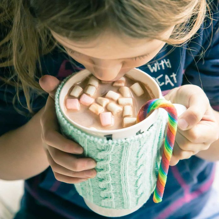 Girl drinking hot chocolate our of a mug with a warmer