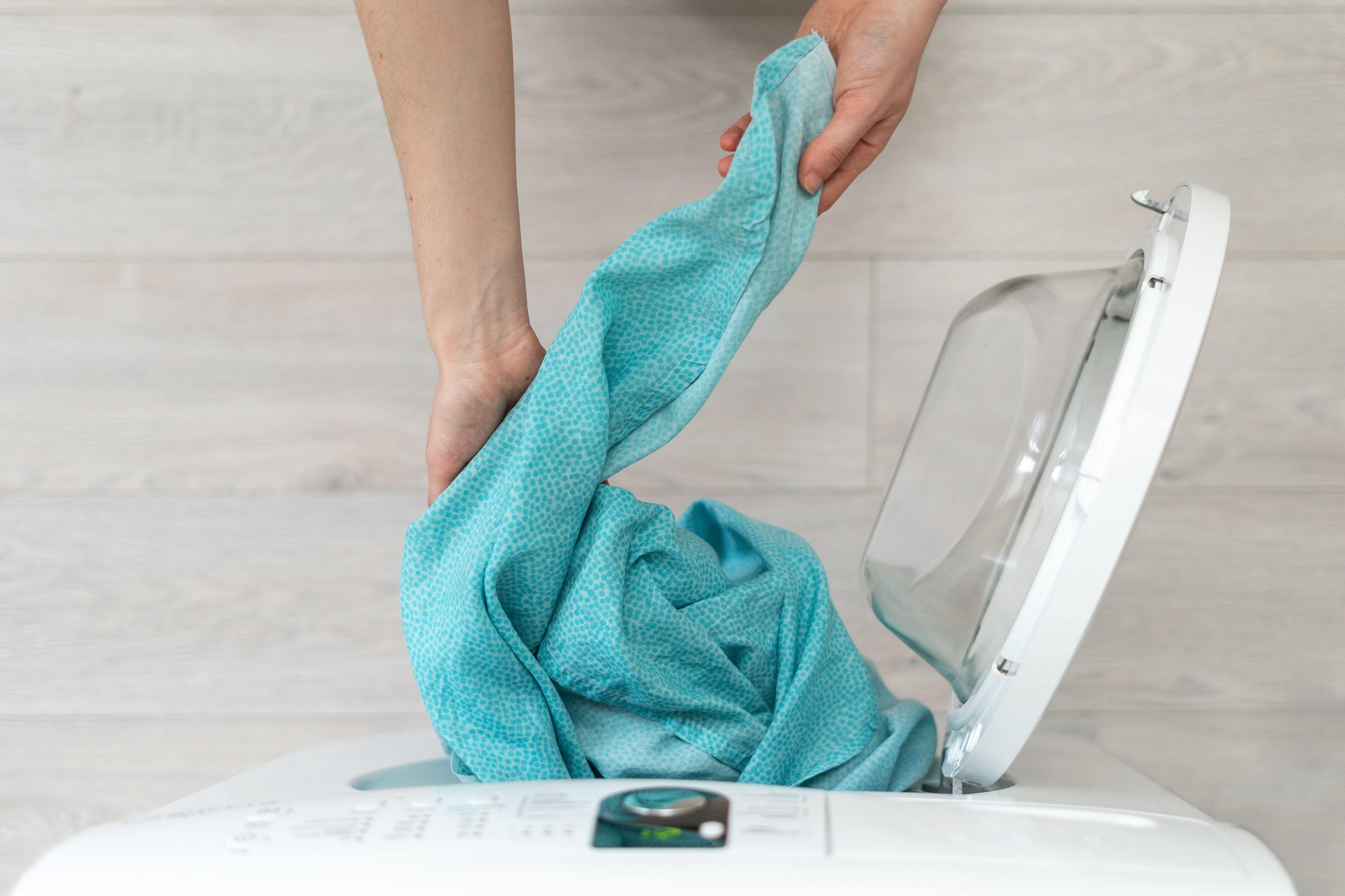 Cropped photo of finished laundry process. High angle above top view of woman hand take out linen from white washing machine standing inside flat with bright interior