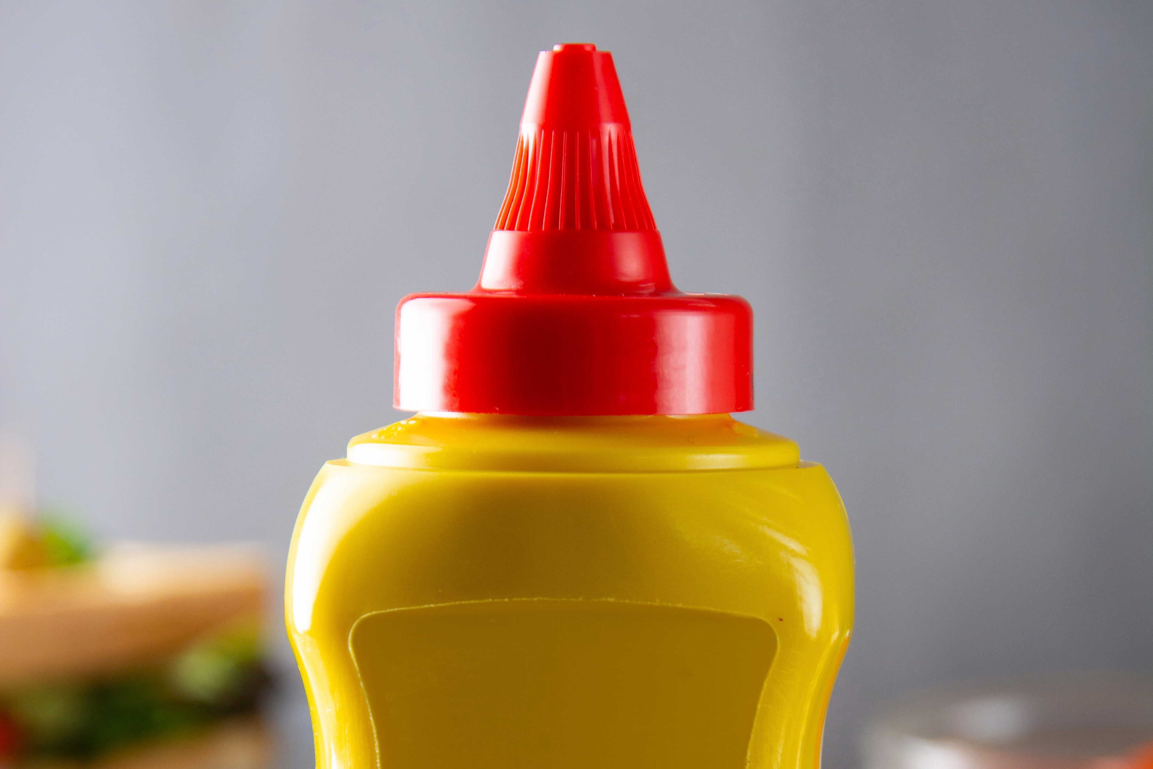Yellow mustard squeeze bottle container with no label. Breakfast sandwich on background. Food product.