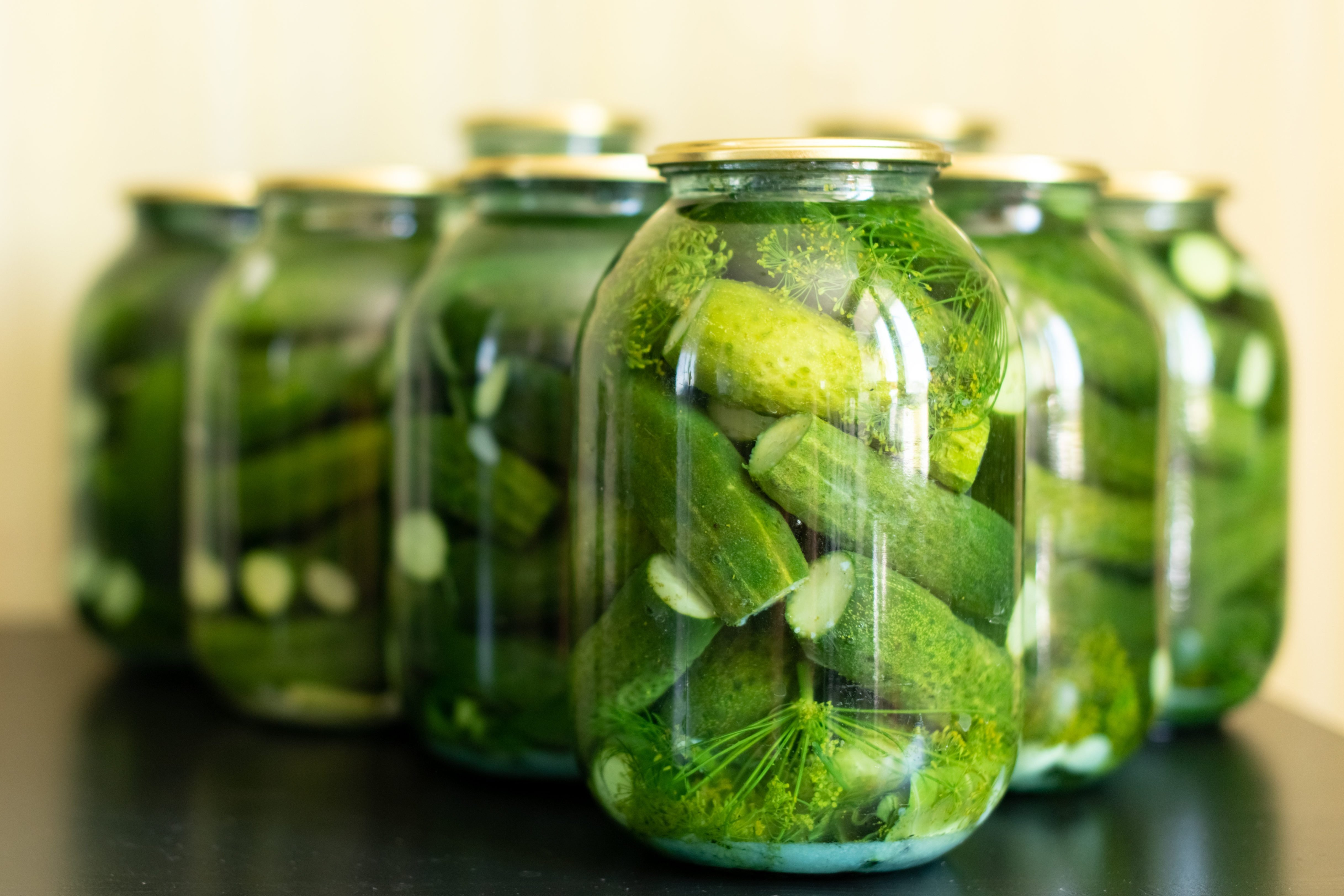 Pickled cucumbers in glass jar on a gray wooden table.