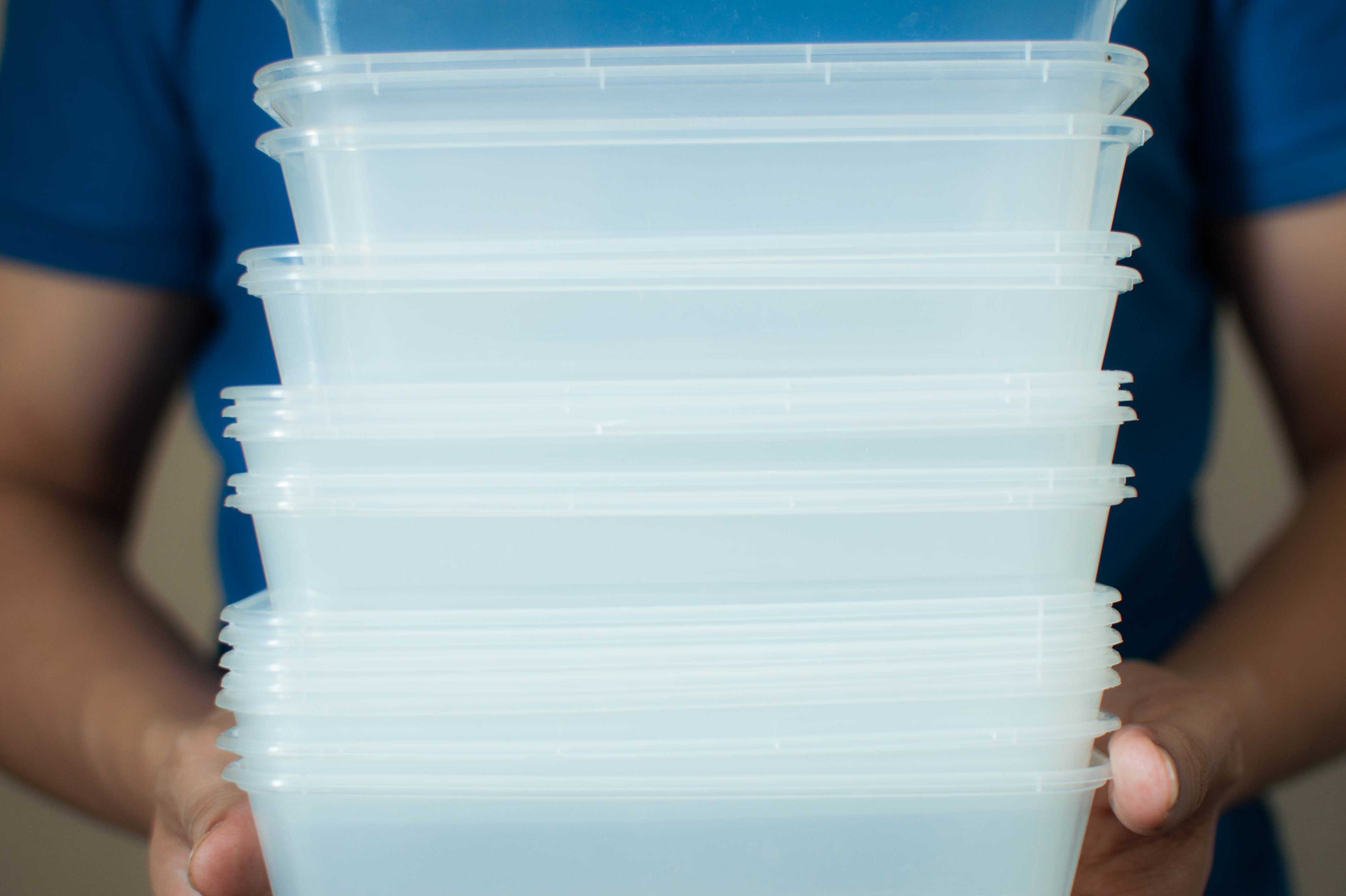 A young man is holding a recyclable plastic food container on a white background