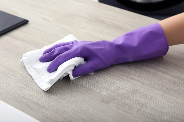 Young woman cleaning table at home