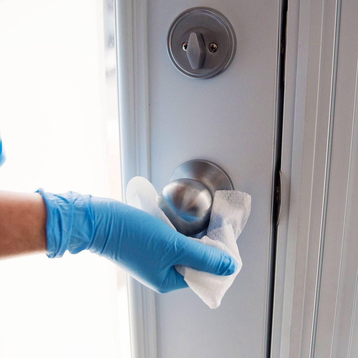 Hands with glove wiping doorknob antibacterial wipe
