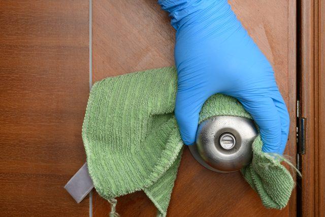 wiping a door lock with disinfectant liquid
