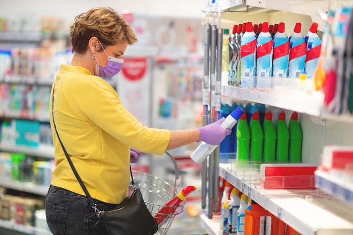 Mid adult woman reading label of disinfectant
