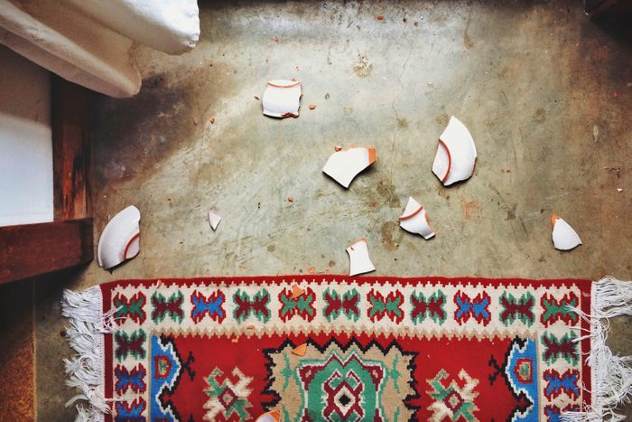 Directly Above Shot Of Broken Plate By Carpet At Home