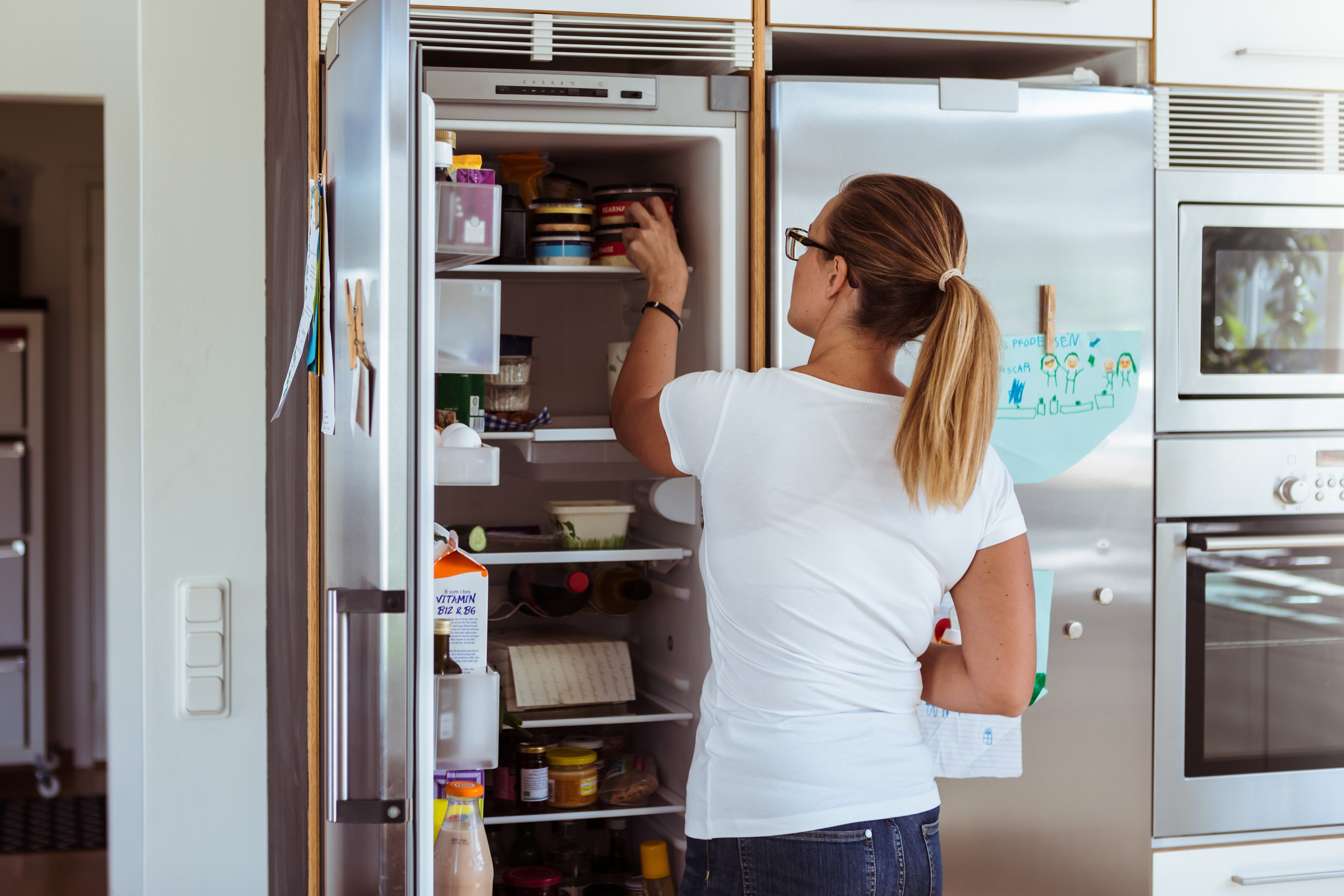 Rear view of woman looking into refrigerator while standing in kitchen