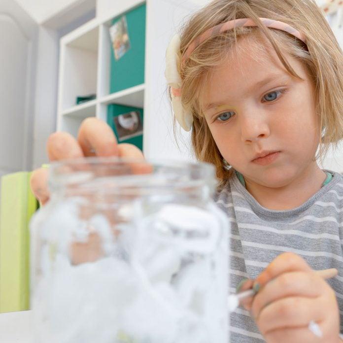 Child painting a jar