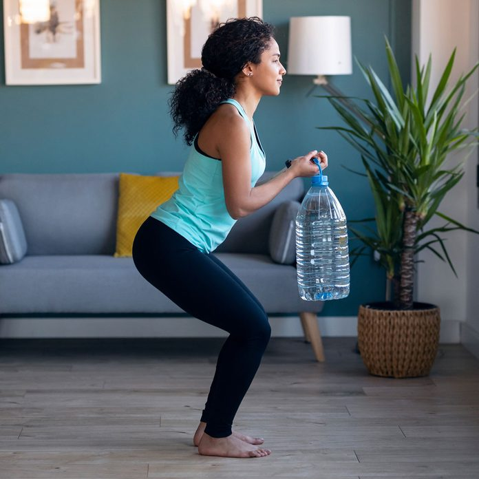 Woman squatting with Bottle Weight Gettyimages 1299959870