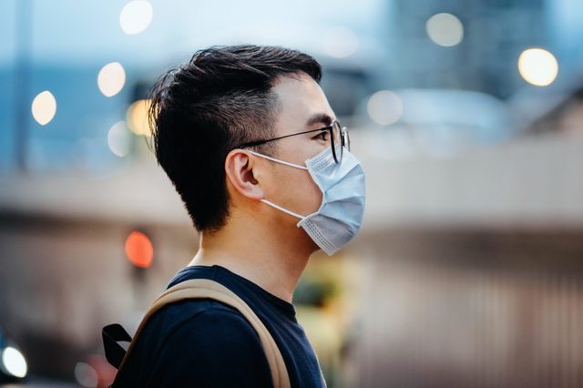 Portrait of young Asian man with face mask to protect and prevent from the spread of viruses in the city
