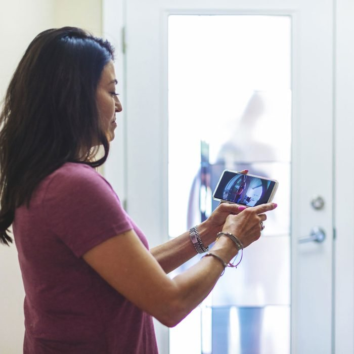 Woman checking smart doorbell