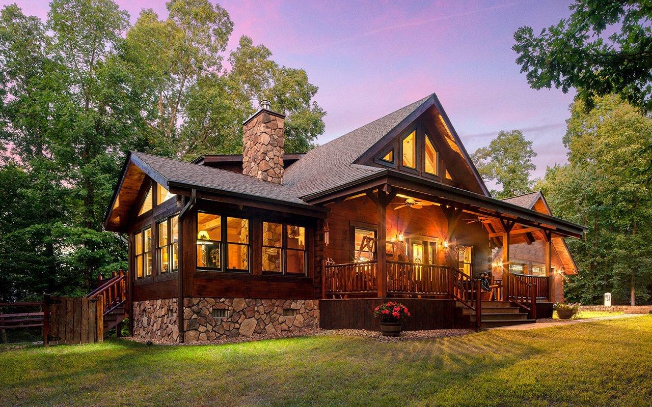 Lit-up log home at dusk