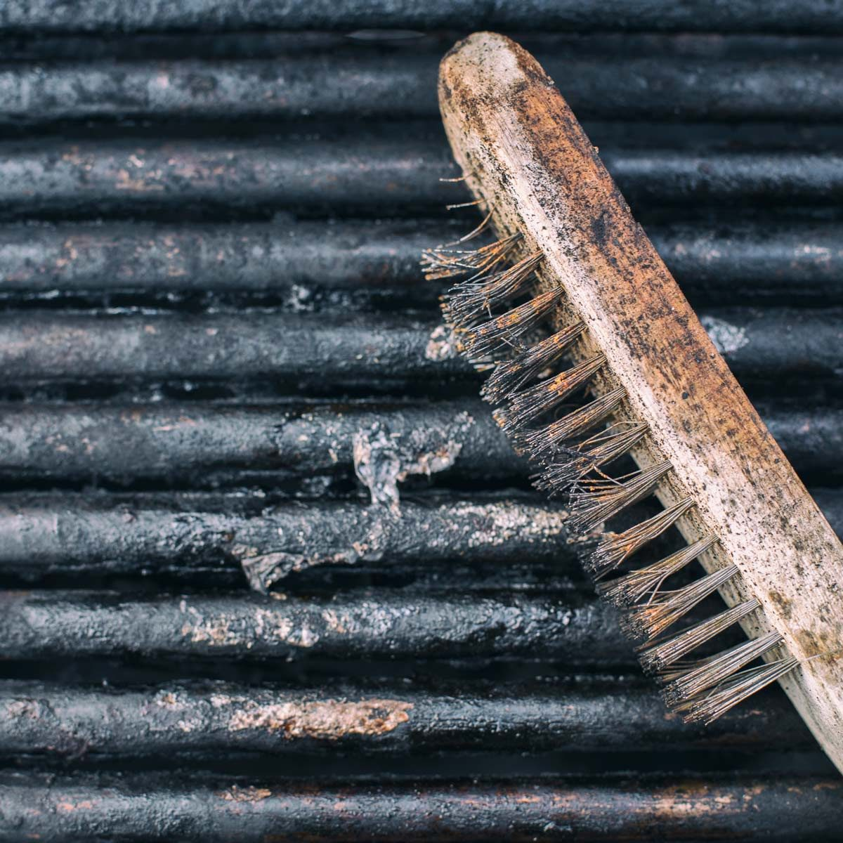 Close-Up Of Dirty used Barbecue Grill and scrubber grill brush