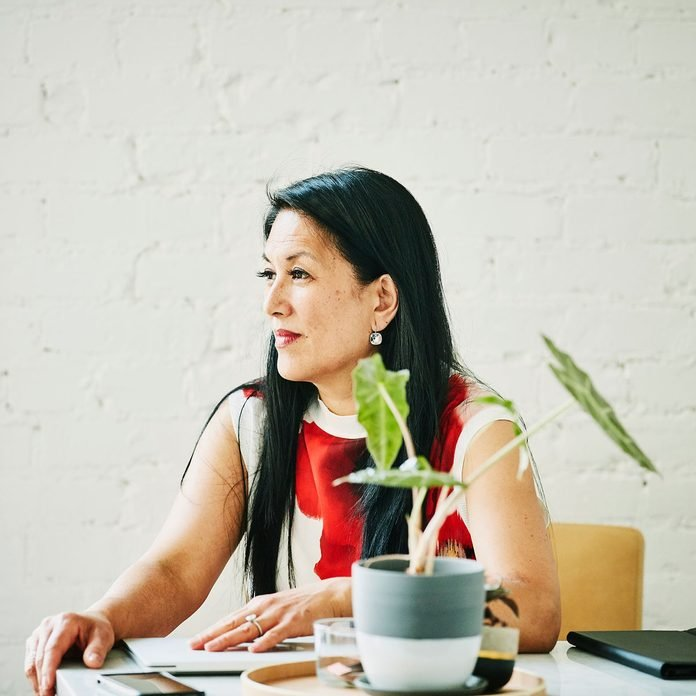 Woman sitting in home office with plant