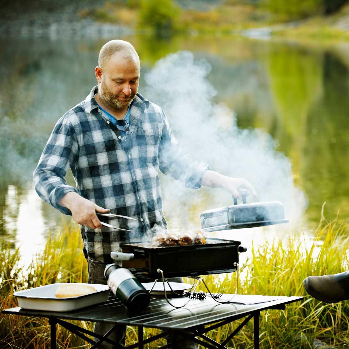 Man grilling by lake