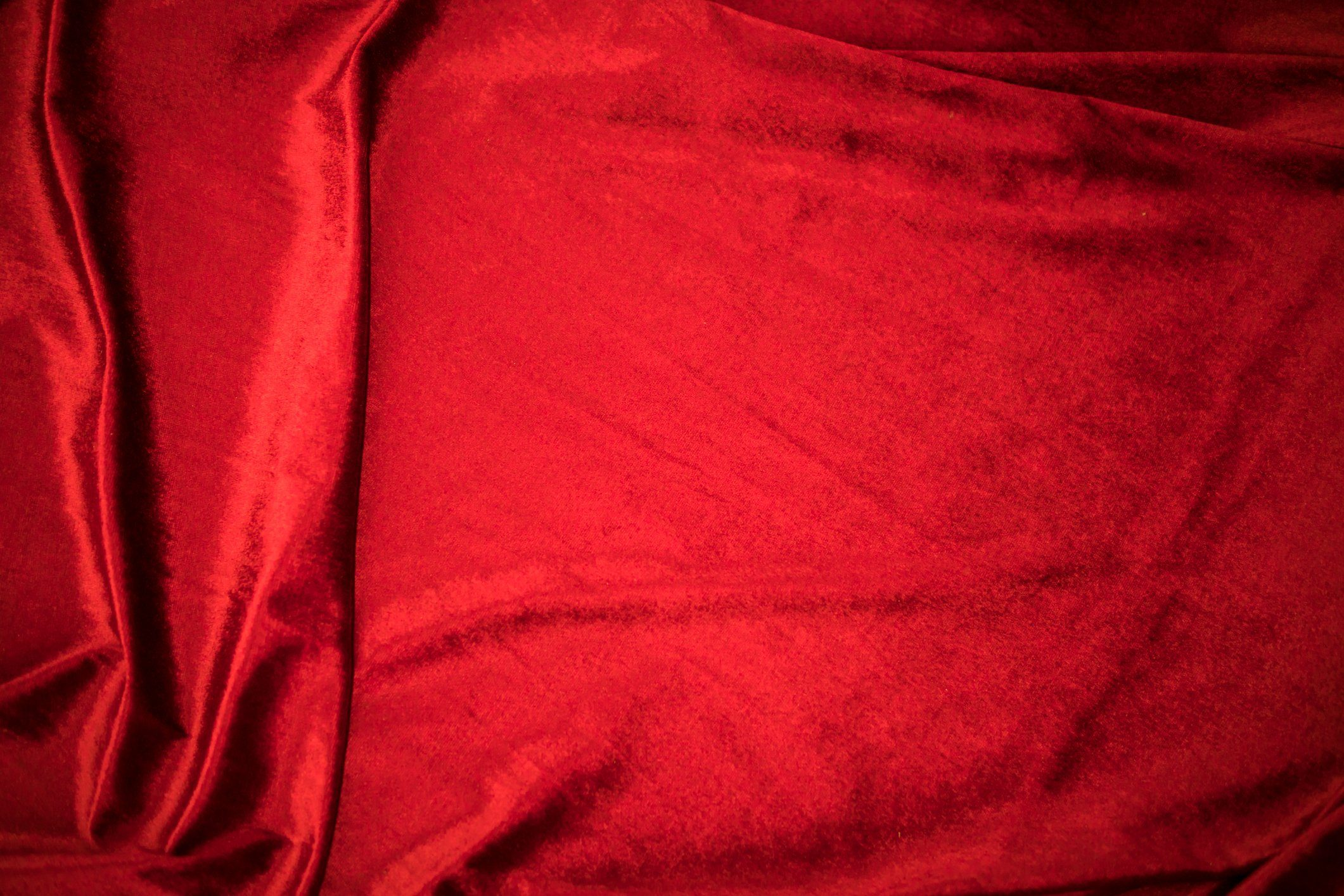 Fold soft waved red velour fabric textured background.