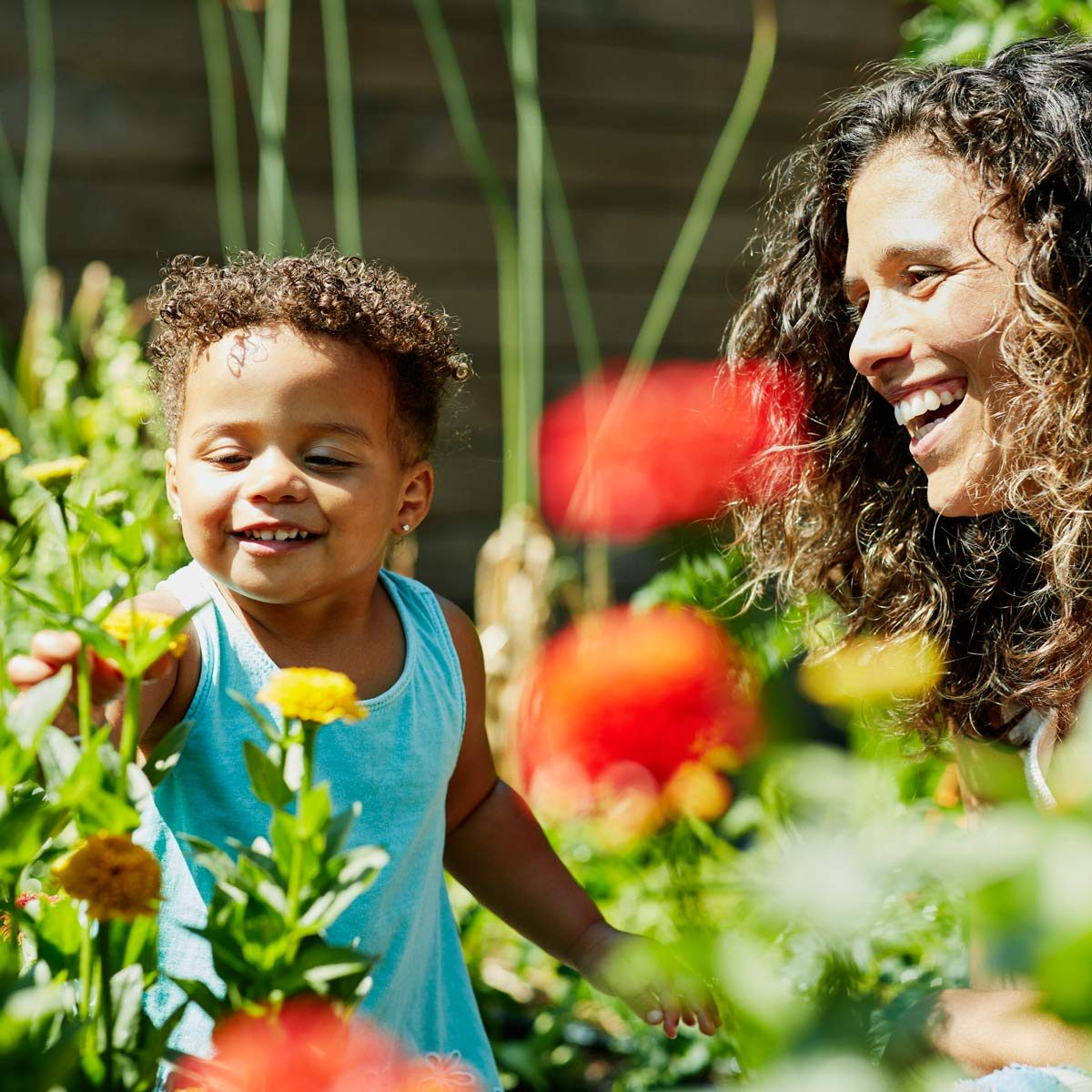 Smiling mother and toddler daughter enjoying flowers growing in backyard garden